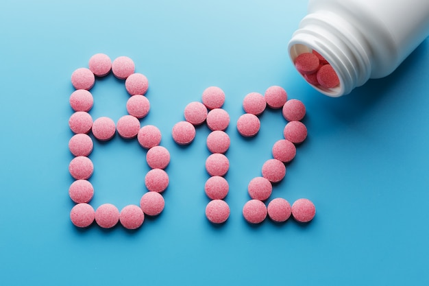 Roze pillen in de vorm van de letter b12 op een blauwe achtergrond