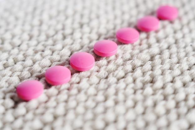Roze pillen op een gebreide achtergrond