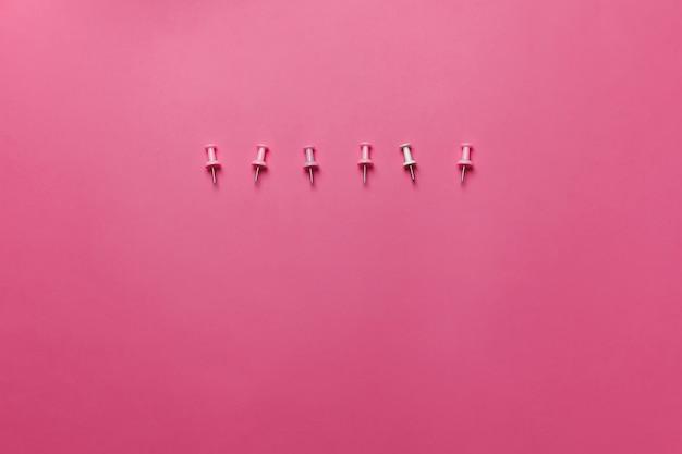 Roze pinnen op de roze achtergrond. horizontaal