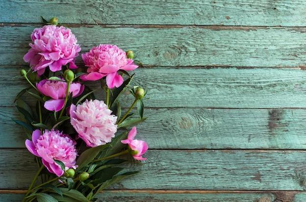 Roze pioen bloemen op blauwe houten tafel