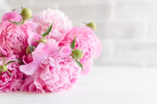 Roze pioen bloemen op witte houten tafel