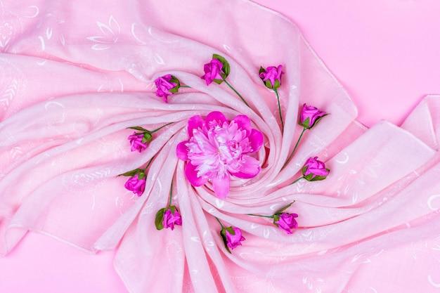 Roze pioen bloemknop en kunstmatige rozen op roze stof