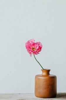 Roze pioen in een vaas bij de muur