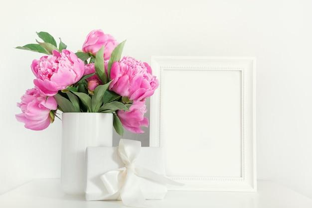 Roze pioen in vaas met cadeau fotolijst op wit.