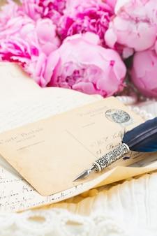 Roze pioen met antieke brief met kopie ruimte en veren pen op wit kant