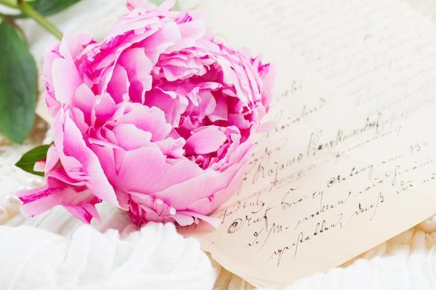 Roze pioen met antieke letter op wit kant