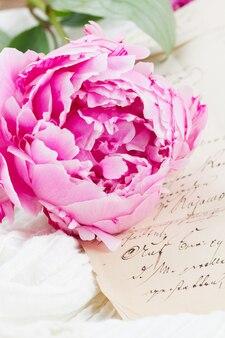 Roze pioen met vintage letter op wit kant