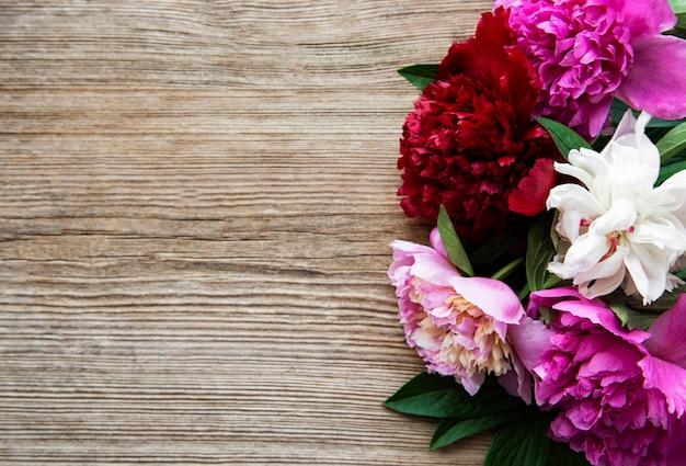 Roze pioenbloemen als rand op een oud houten oppervlak