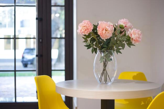 Roze pioenrozen in een glazen vaas op houten tafel