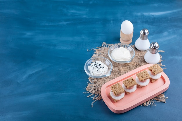 Roze plaat van gesneden brood met witte kaas en ei op blauwe ondergrond.
