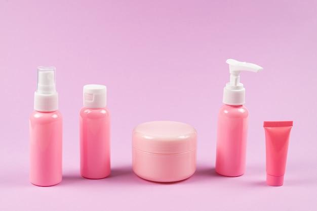 Roze plastic flessen voor hygiëneproducten, cosmetica, hygiëneproducten op een roze achtergrond.
