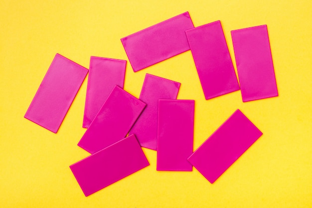 Roze plastic platte rechthoeken zijn chaotisch verspreid op een gele achtergrond.