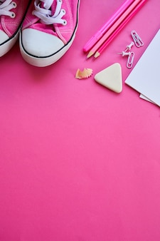 Roze plat lag terug naar schoolconcept, school- en kantoorbenodigdheden met kopieerruimte. veel verschillende schrijfwaren op een kleurrijke achtergrond