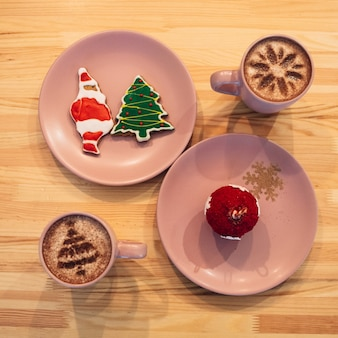 Roze platen met kerstfeestjes staan tussen kopjes met koffie op houten tafel