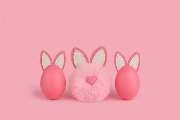Roze pluizig konijntje van pasen en twee eieren met oren op een roze achtergrond.