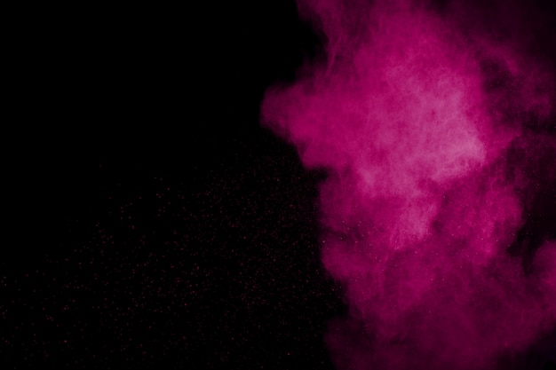 Roze poederexplosie op zwarte achtergrond.
