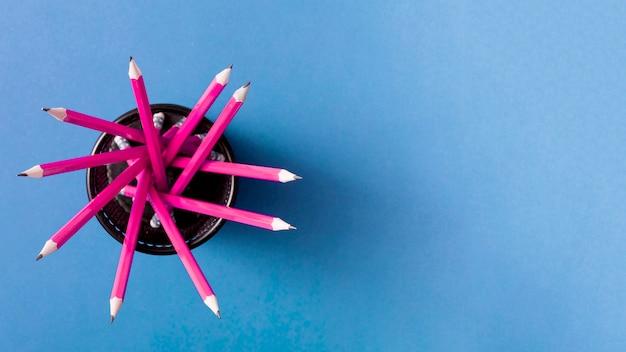 Roze potloden in de houder tegen blauwe achtergrond