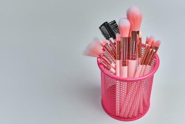 Roze professionele cosmetica make-up kwasten in een roze doos op een witte achtergrond met vrije ruimte.