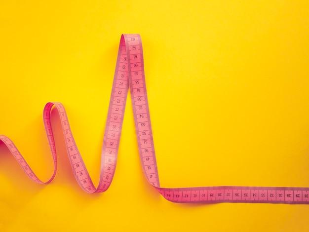 Roze pulsvormige meetlint geïsoleerd op geel