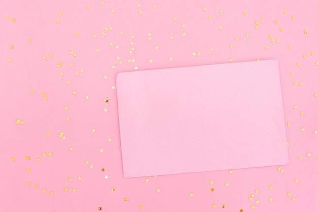 Roze ranunculus bloemen, geschenk of huidige vak en lege kaart met envelop op tafel.