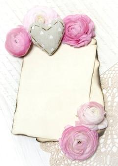 Roze ranunculus bloemen, stoffen hart en papier kopiëren ruimte muur op een gehaakt kleedje bovenaanzicht
