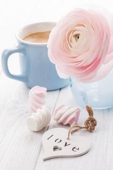 Roze ranunculus en mok koffie