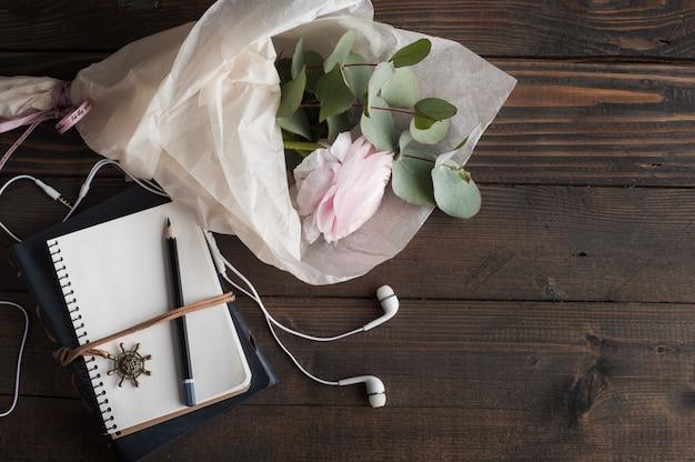 Roze ranunculus, open notitieboekje en fiets