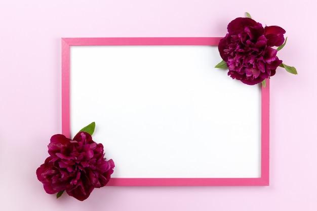 Roze rechthoekig frame met schoon wit centrum en pioenrozen aan de zijkanten op pastelroze