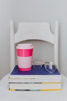 Roze reismok op een stapel handboeken