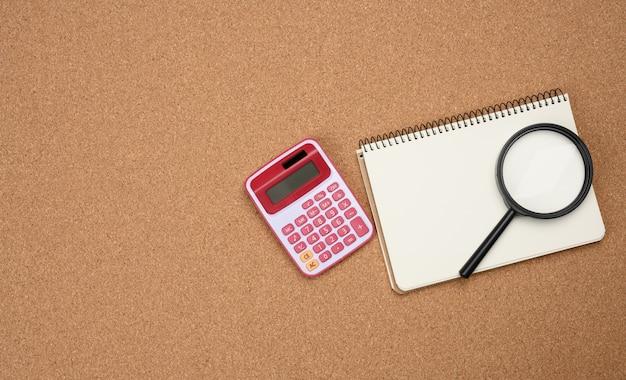 Roze rekenmachine, notitieboekje met lege witte bladen en zwart vergrootglas op een bruine achtergrond. banner voor bedrijven, bovenaanzicht