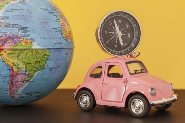Roze retro auto en kompas met wereldbolgebied op geel