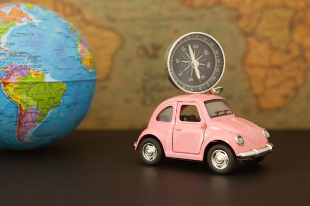 Roze retro auto met bol van de wereldbol