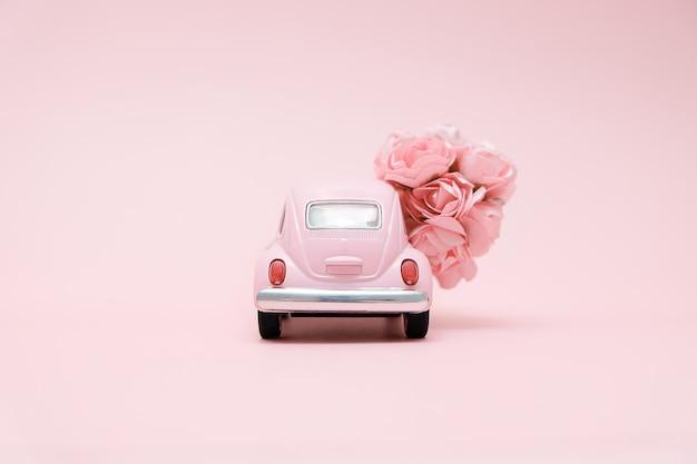 Roze retro speelgoedauto leveren boeket bloemen