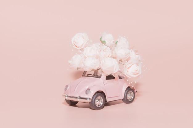 Roze retro speelgoedauto met boeket van wit