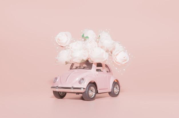 Roze retro speelgoedauto met boeket van witte rozen op roze achtergrond.