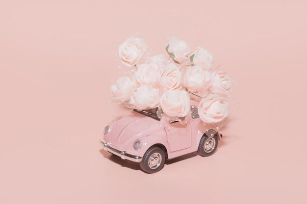 Roze retro speelgoedauto met boeket van witte rozen op roze.