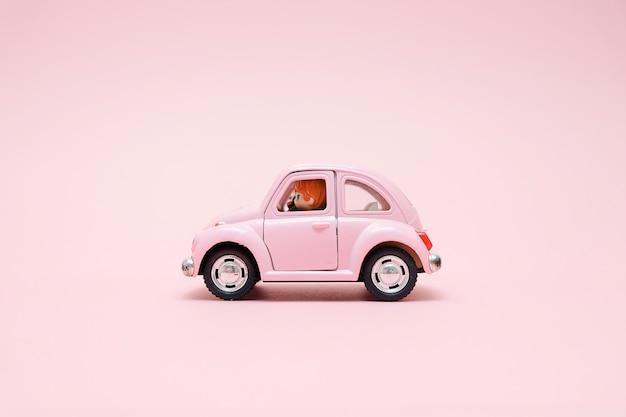 Roze retro speelgoedauto met schattige paar