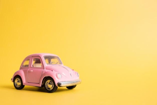 Roze retro speelgoedauto op geel. zomer reizen concept. taxi.