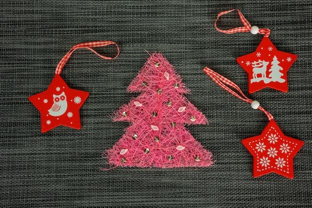 Roze rieten boom versierd met rode sterren. kerstmis en nieuwjaar concept.