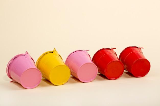 Roze, rode en gele emmers op een gele muur
