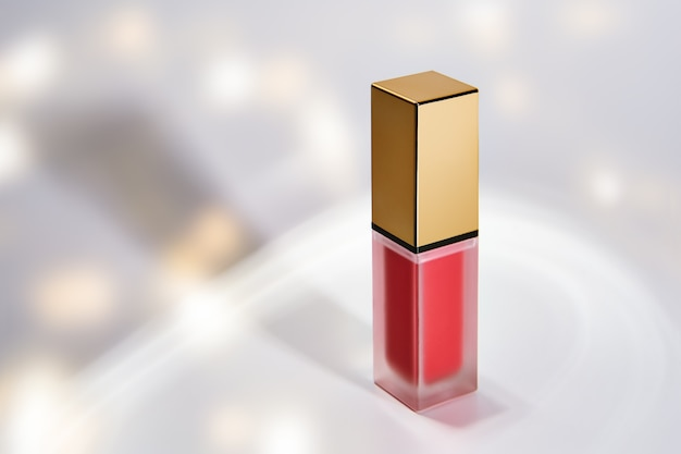 Roze rode vloeibare lippenstift tube op een witte sprankelende achtergrond met copyspace