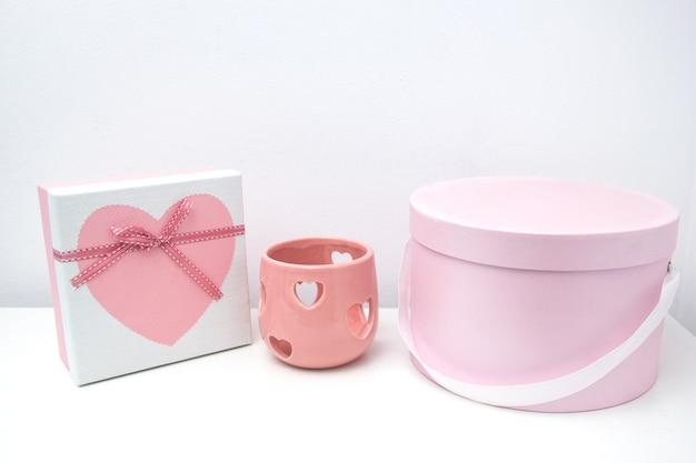 Roze romantische geschenkdoos met witte satijnen strik op een lichtblauwe houten stoel