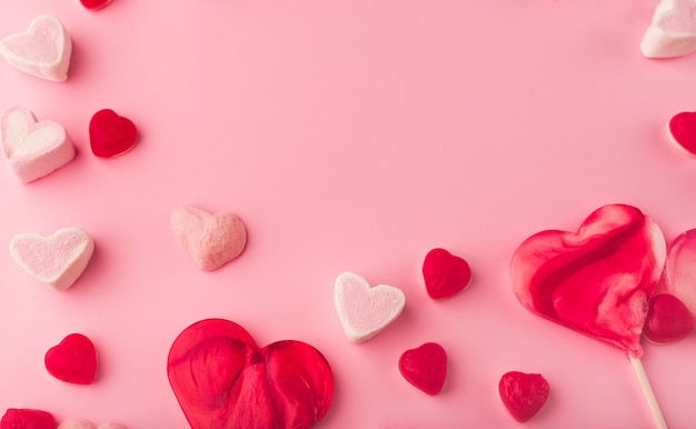 Roze romantische vakantie achtergrond met hartvormige zoete snoepjes. decoratieve kaart voor valentijnsdag met ruimte voor tekst. liefdesthema.