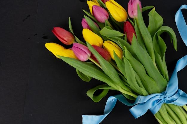 Roze, rood en violet tulpen bloemen boeket met hartjes op zwarte achtergrond