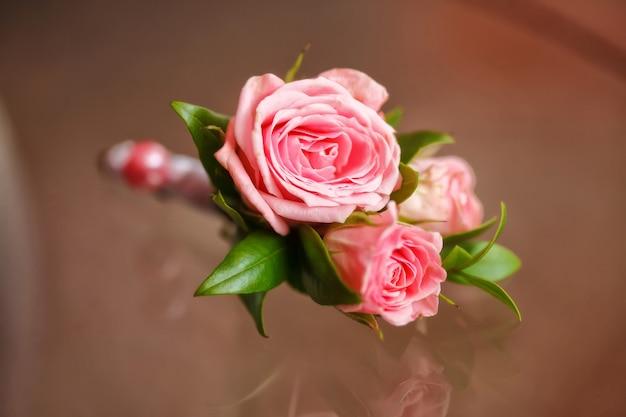Roze roos boutonniere voor bruidegom