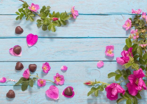 Roze roos en chocolade op houten ruimte