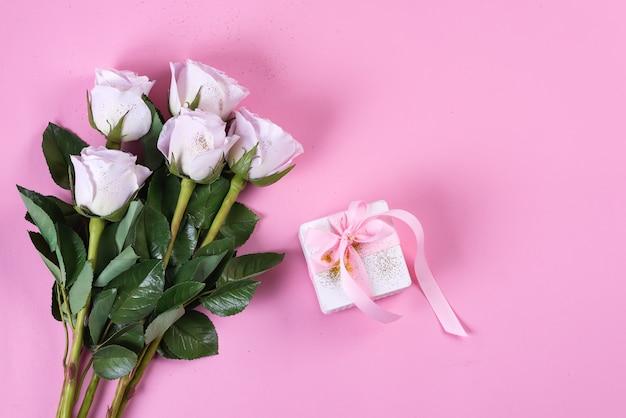 Roze roos en witte geschenkdoos met roze lint
