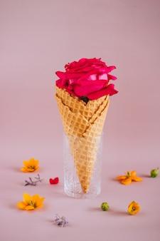 Roze roos in ijs op roze met kleurrijke bloemen, kopie ruimte