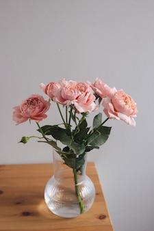 Roze roos in vaas op houten tafel op grijze muur verticaal