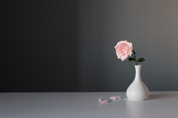 Roze roos in witte vaas op grijze achtergrond